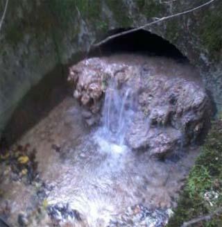 Avant l'introduction des bactéries, les réseaux d'assainissement du tunnel du Vuache avec le dépôt de calcite - © ATMB